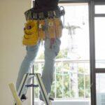 脚立に乗り工具で室内作業をする男性