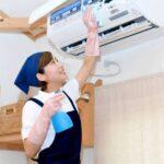 エアコンの清掃をする三角巾を着けた女性